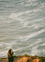 Woman taking pictures of the sea