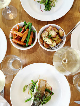 overhead view of restaurant lunch, with seafood, vegetables and white wine