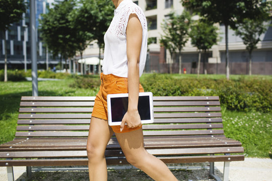 Woman walking in the park, holding a digital tablet