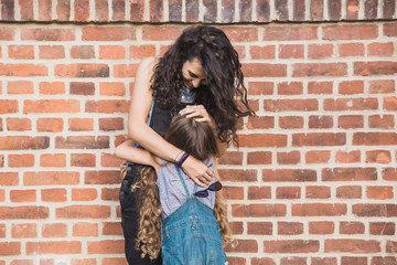 Mother and daughter embracing in front of a brick red wall