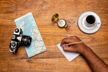 Man planning a tripView of a world map, white paper, coffee and a vintage camera