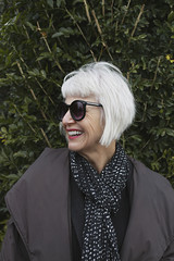 stylish and attractive older woman outdoors wearing a scarf and sunglasses