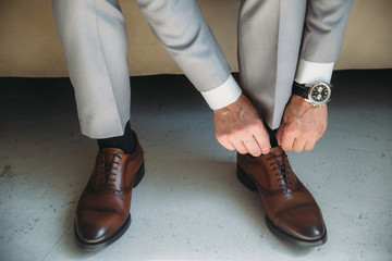 man wears shoes. Tie the laces on the shoes. Men's style. prepare for work, to the meeting