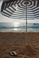 Umbrella and thongs on the beach