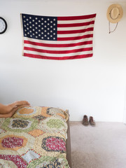 American flag and straw hat hanging on wall of bedroom