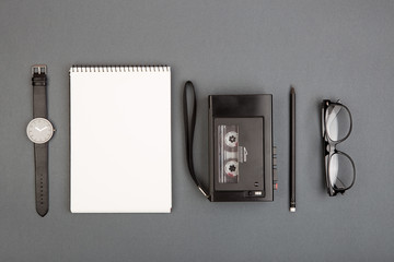 Journalist workplace - tape recorder, notepad on the grey background, flat view