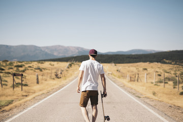 Man with skateboard on road