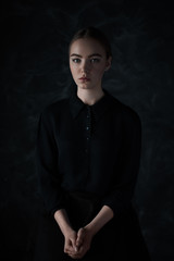 portrait of a beautiful young model in a dark dress in the studio