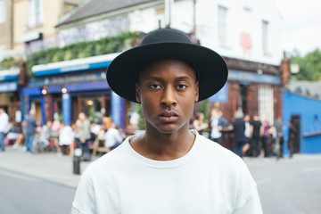 London Street Style - Cool Young Fashionable Black Man Standing in Busy Street