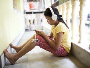 Teenage girl using smartphone and listening music
