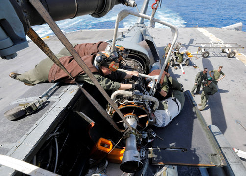 Marine crew chiefs and mechanics removes a faulty engine from a CH-53E Super Stallion aboard the USS Kearsarge as it heads towards the trailing end of Hurricane Maria to assist people in the Caribbean Sea