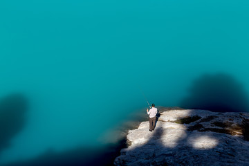 un homme habillé en blanc pêche depuis un rocher gris dans un lac bleu émeraude
