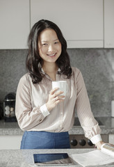 Smiling asian woman having coffee in her modern kitchen.