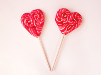 Two red heart shaped lollipops on light background. Valentines Day background