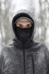 Portrait of a young man standing outside covered in the falling snow
