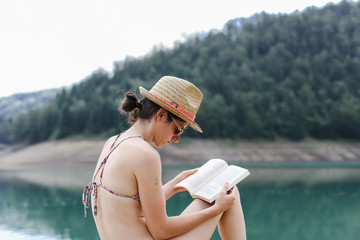 Young woman reading a book, near the lake