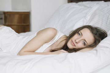 Beautiful calm girl lying on white bed