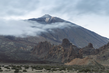 Semi-Desert landscape with Teide peak covered by clouds