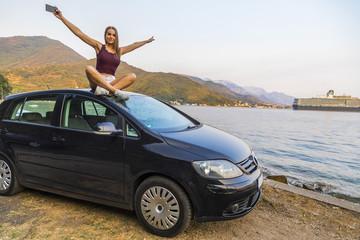 девушка сидит на крыше автомобиля на фоне моря в Европе