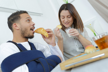 young couple eating croissants on breakfast in bed