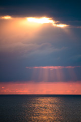 A fascinating seascape with dramatic clouds and sunlight between them