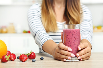 Young woman drinking smoothie in the kitchen