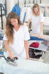 2 laundry employees smiling while ironing