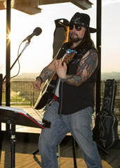 Musician performing at a local venue back lit by the setting sun coming through the windows