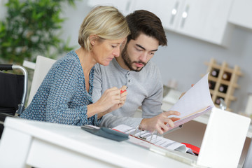 young home help employee with mature woman accounting