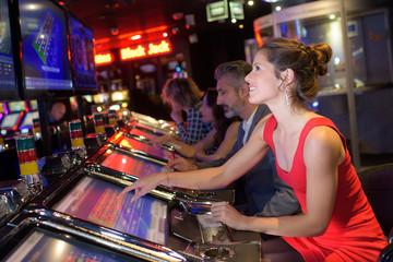 cheerful pretty woman playing slot machines in casino