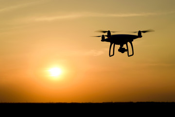 Quadrocopters silhouette against the background of the sunset