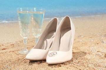 Beautiful high heel shoes with rings and glasses on sand. Beach wedding concept