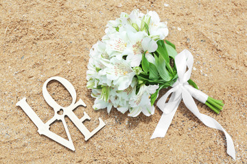 Beautiful bouquet and word LOVE on sand. Beach wedding concept