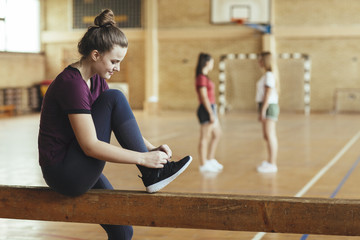 Girl Tying Shoelace in School Gym