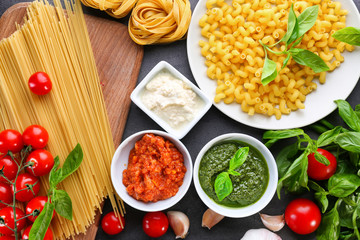 Composition with pesto, bolognese and white sauces for pasta in bowls on table