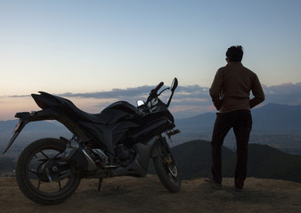 A silhouette of a man and his motorbike on top of a hill.