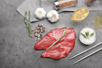 Composition with two raw steaks, rosemary and spices on grey background