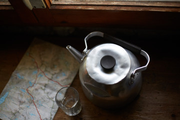 Old aluminum kettle with glass and map seen from above