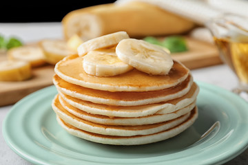 Plate with yummy banana pancakes on kitchen table, closeup