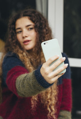 Brunette woman takes a selfie. Focus on the phone.