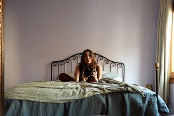 Beautiful woman making selfie in mirror using digital camera