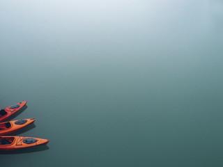 Orange kayaks tied together in water