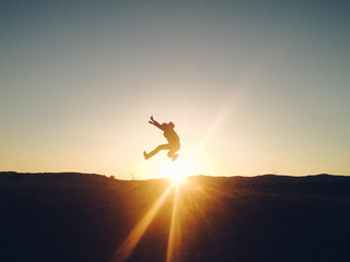 Silhouette man jumping outdoor in the sunset