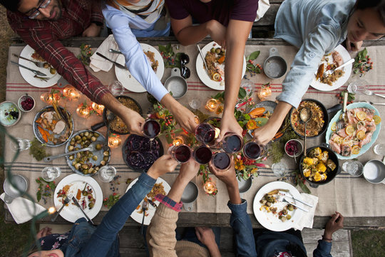 Overhead view of friends making a toast at lunch party