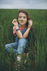 Portrait of cute calm girl with blade of grass near nose