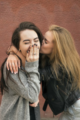 Blonde girlfriend kissing brunette with eyes closed
