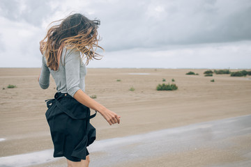 woman playing and jumping with water on the beach