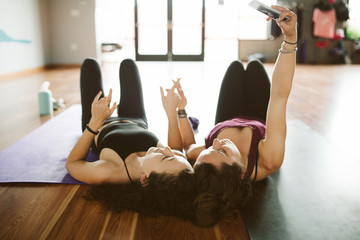 Two female friends lying on floor of yoga studio after class taking selfie.