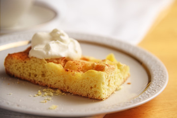 piece of homemade apple cake with whipped cream on a white plate, close up, copy space