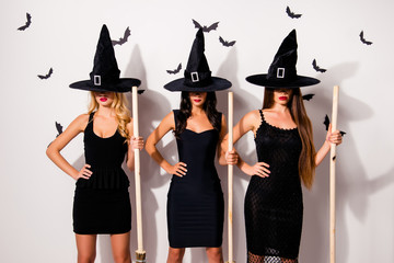 Three mysterious mistress vampire monsters in elegant costume clothing in long wizard headwears, covered their eyes, with brooms, hands on waist, waiting for you at spooky night, whtite background